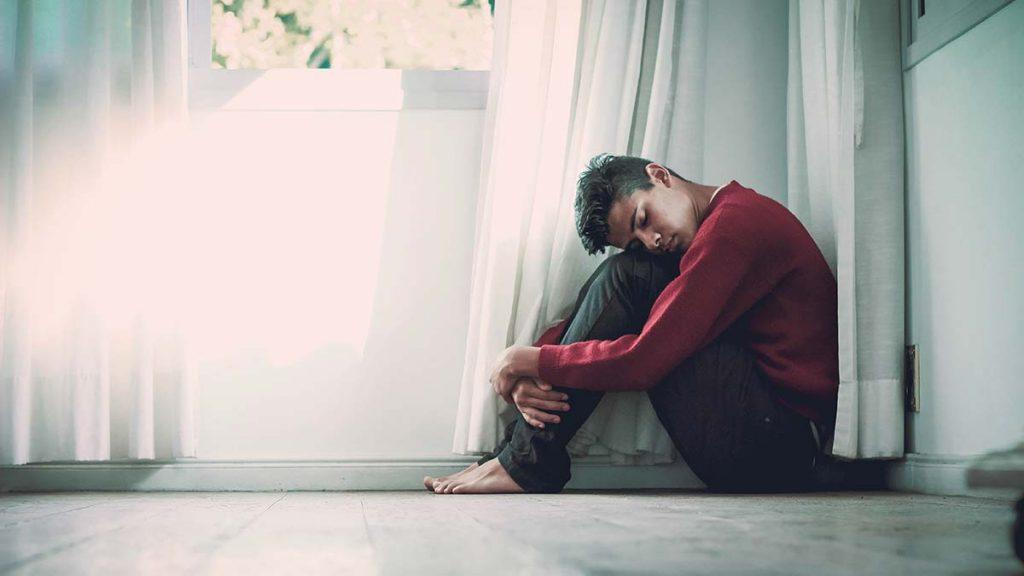 Teen boy sitting below a window