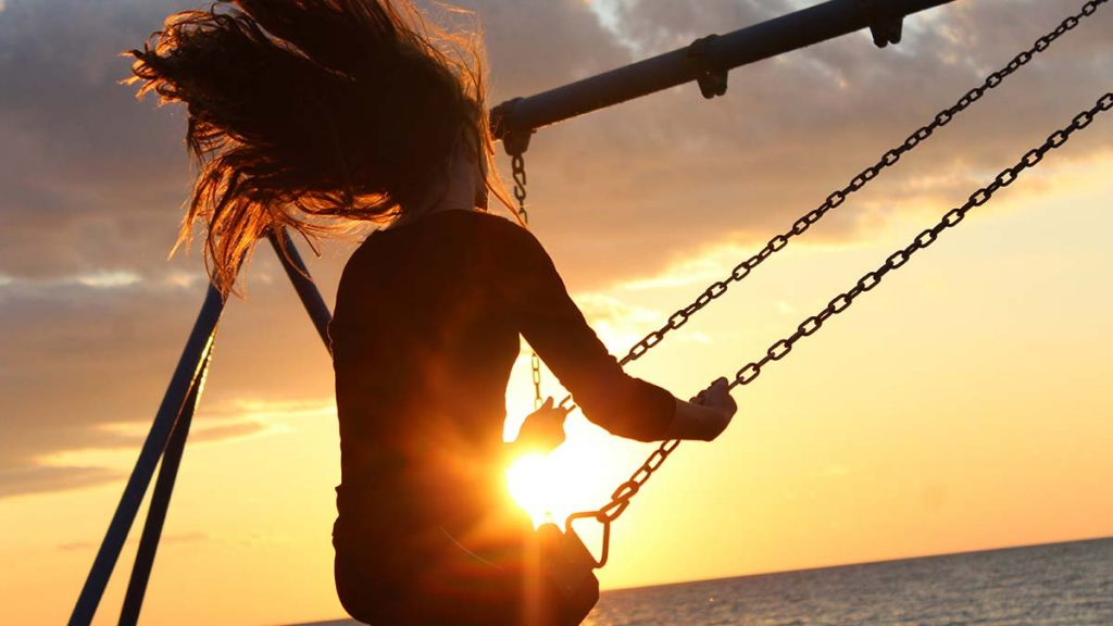 Girl swinging in the sunset