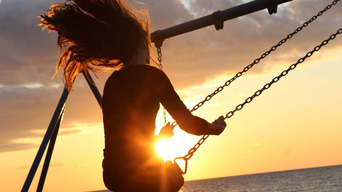 Girl swinging in the sunset