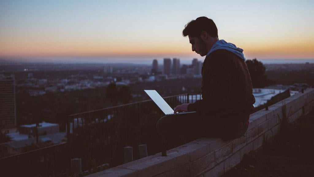 Young man with his laptop sitting on a ledge