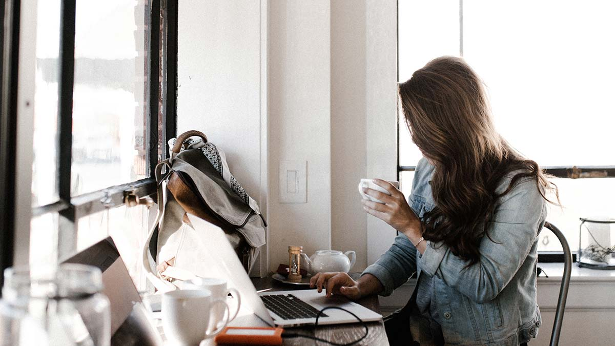 Woman at her computer with a cup of coffee