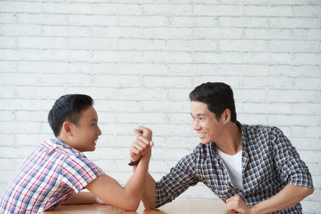 Cheerful teenage boy arm wrestling with his father