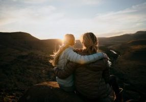 Caucasian Mother and Daughter bonding and hugging while enjoying the beautiful view after a mountain hike during sunset.